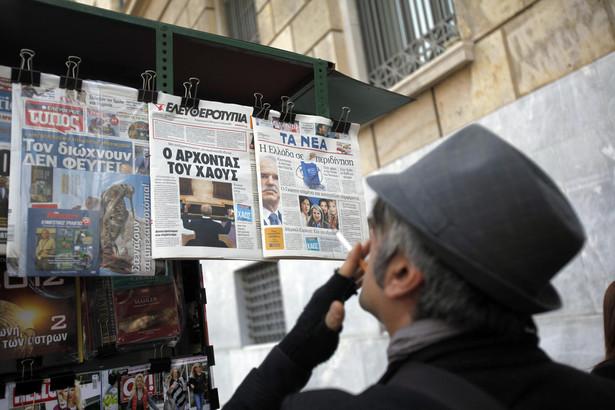Przechodzieńz papierosem czyta tytuły dzienników w kiosku ulicznym w Atenach, Grecja, 2 listopada 2011. Premier Grecji Jeorjos Papandreu zaproponował referendum w sprawie przyjęcia pakietu pomocowego dla pograżonego od dwóch lat w kryzysie kraju, czym zaskoczył opinię publiczną i przedstawicieli unijnych.