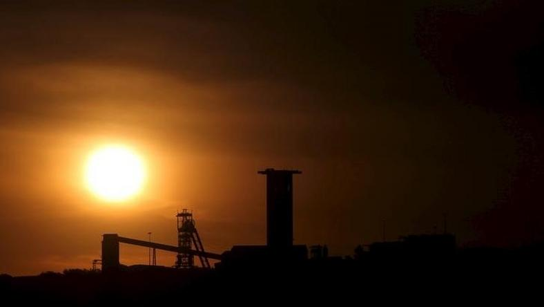 The sun sets behind a shaft outside the mining town of Carletonville, west of Johannesburg, July 7 2015. REUTERS/Siphiwe Sibeko