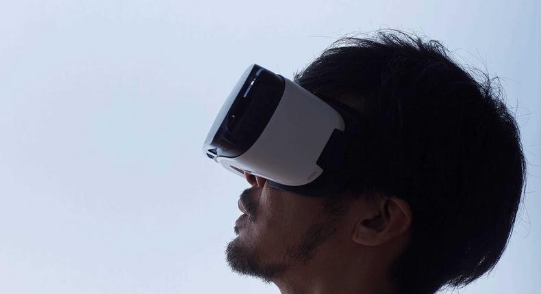 A stock image shows a man using a virtual reality headset.