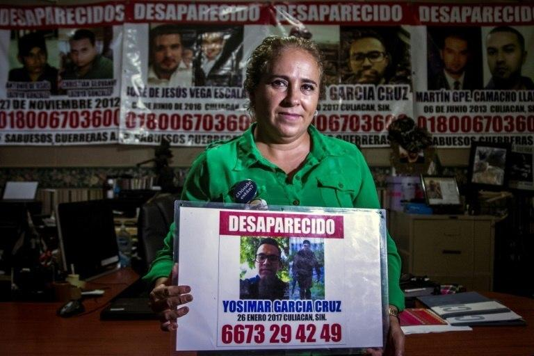 Maria Isabel Cruz holds pictures of her son, a Culiacan policeman who went missing last year; she now leads a group of some 100 women with similar stories who comb the countryside, looking for the mass graves where cartel hitmen bury their victims