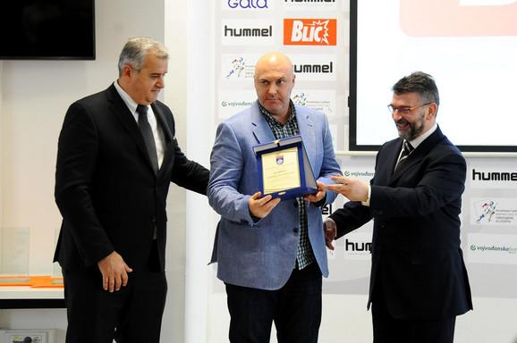 Čelni ljudi RSS-a, predsednik Saveza Božidar Đuković i generalni sekretar Mazlam Džemailoski uručuju priznanje uredniku sportske rubrike
