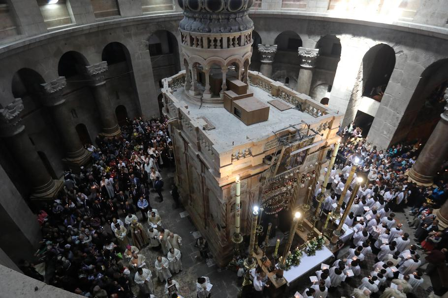 Christian worshippers surround the Edicule as they take part in a Sunday Easter mass procession in t