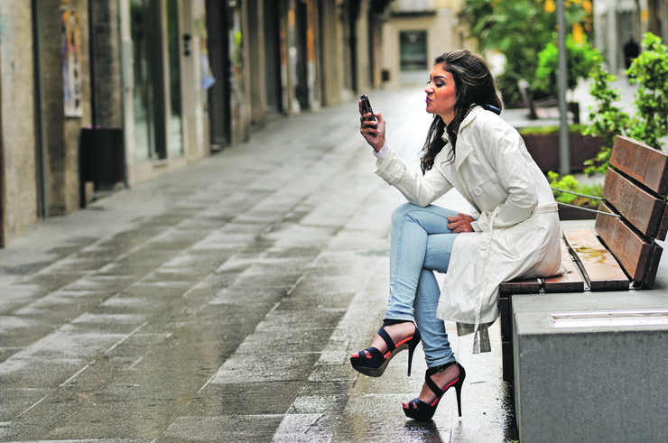 stock-photo-portrait-of-beautiful-young-woman-in-urban-background-talking-on-phone-170863106