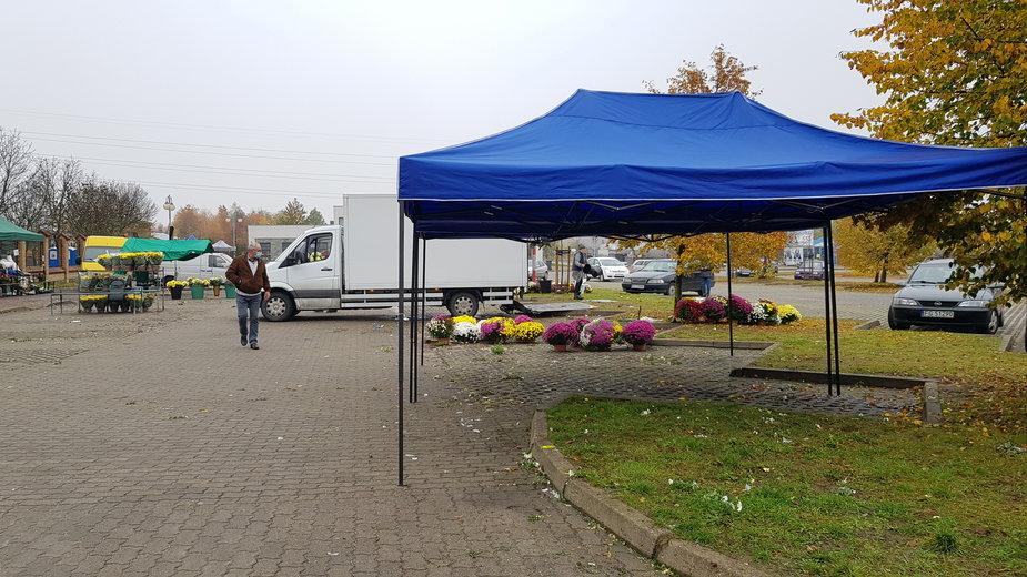 Sprzedawcy pakują kwiaty przy cmentarzu w Gorzowie