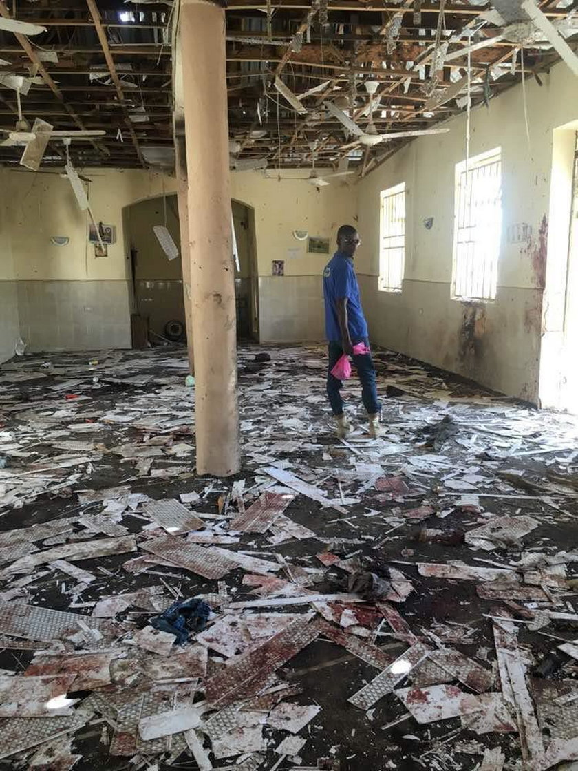 A man inspects the damage inside a mosque at the site of a suicide bomber attack in Mubi in Adamawa