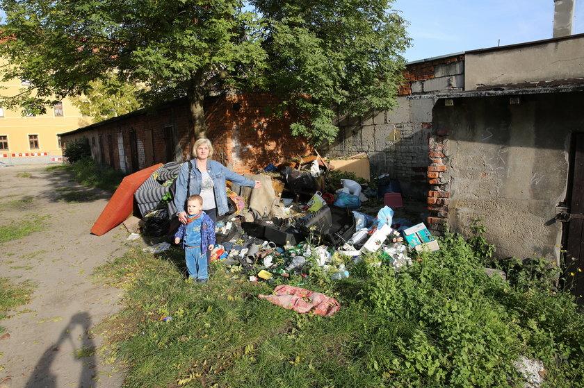 Kobieta z dzieckiem przy śmieciach