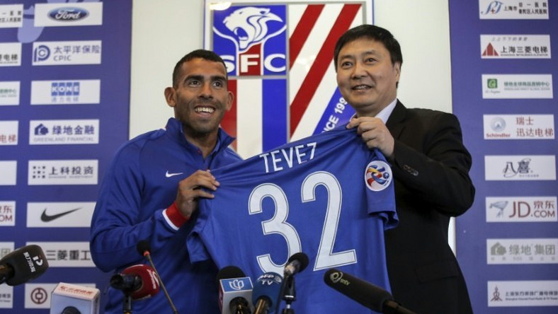 Argentine striker Carlos Tevez (L) poses with his No. 32 shirt of his new club Shanghai Shenhua during a press conference in Shanghai on January 21, 2017