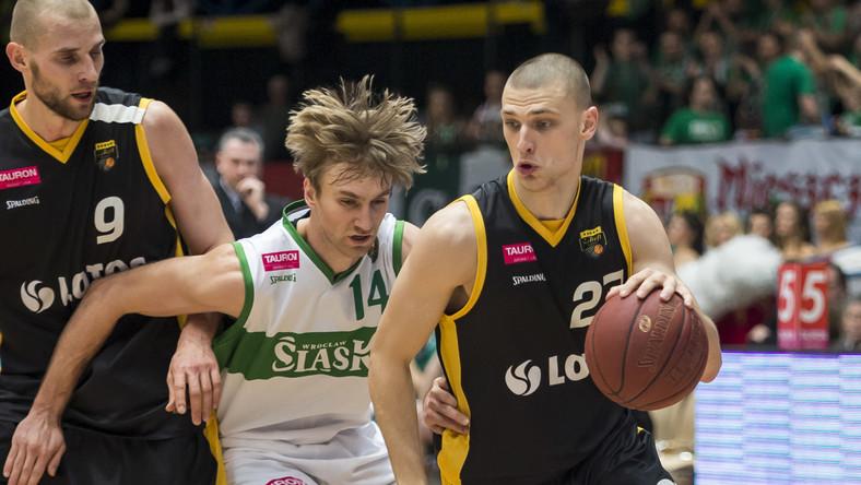Koszykarz Śląska Wrocław Denis Ikovlev (C) walczy o piłkę z Pawłem Leończykiem (L) i Michałem Michalakiem (P) z Trefla Sopot