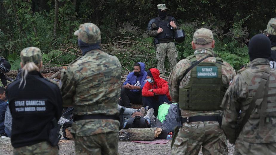 Grupa uchodźców i funkcjonariusze Straży Granicznej na granicy polsko-białoruskiej