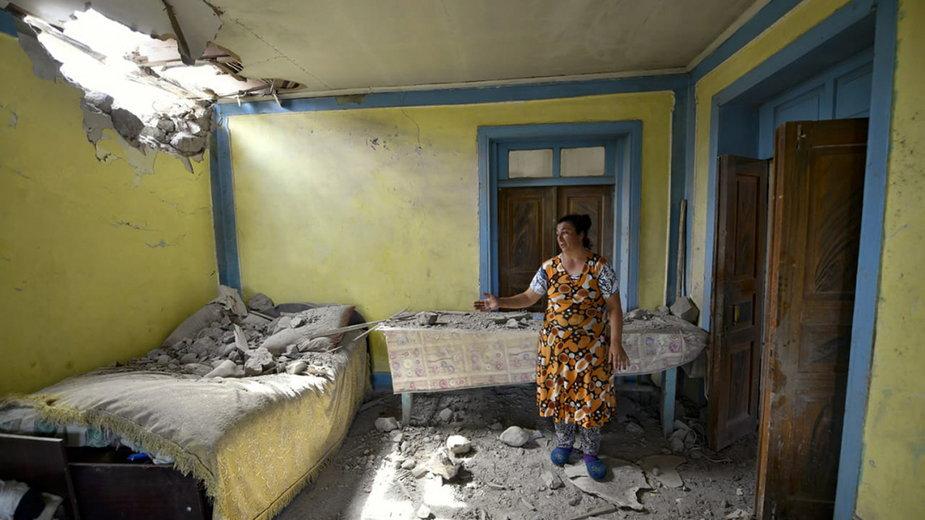 Kobieta pokazuje skutki bombardowania w regionie Towuz w Azerbejdżanie