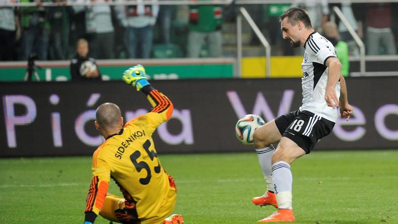Piłkarz Legii Warszawa Michał Kucharczyk (P) w ataku na bramkę Andreja Sidelnikowa (L) z kazachskiego FK Aktobe