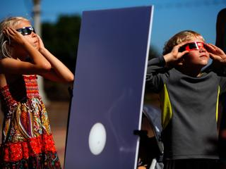 A reflected image of the sun is seen on a white board as kids look up to view the beginning a partia
