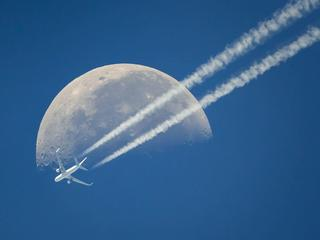 A commercial airplane flies past the moon above Geneva