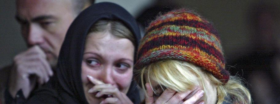 Women mourn during commemoration ceremony at the Dubrovka Theatre in Moscow