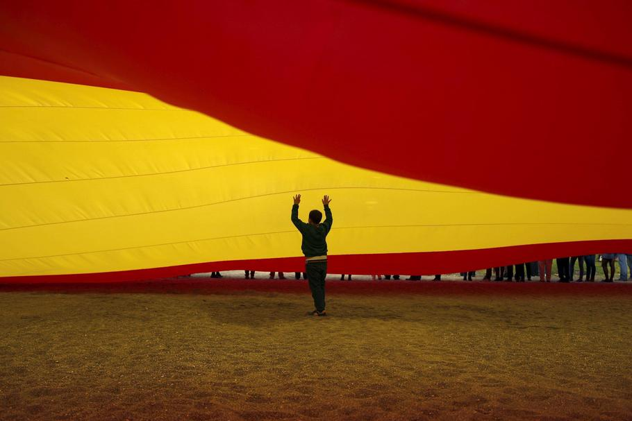 A child walks under a giant Spanish flag unfurled by supporters of Spain's Prime Minister Rajoy to s
