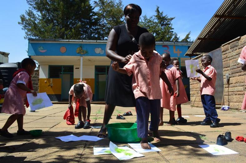 A teacher helps pre-primary school pupils during a class activity at the Kenya Science Primary School (Twitter)