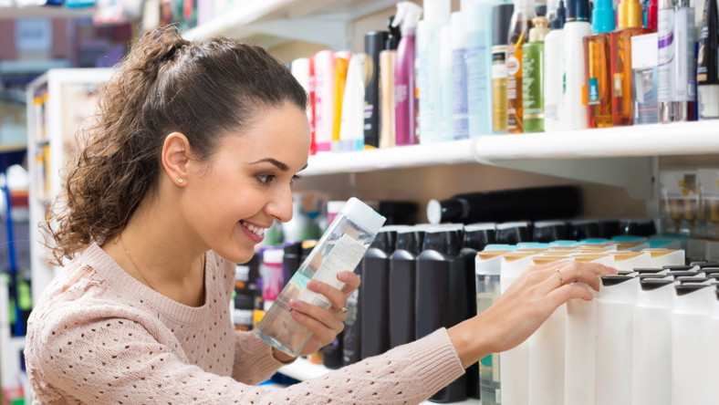 Kobieta wybiera kosmetyki do włosów