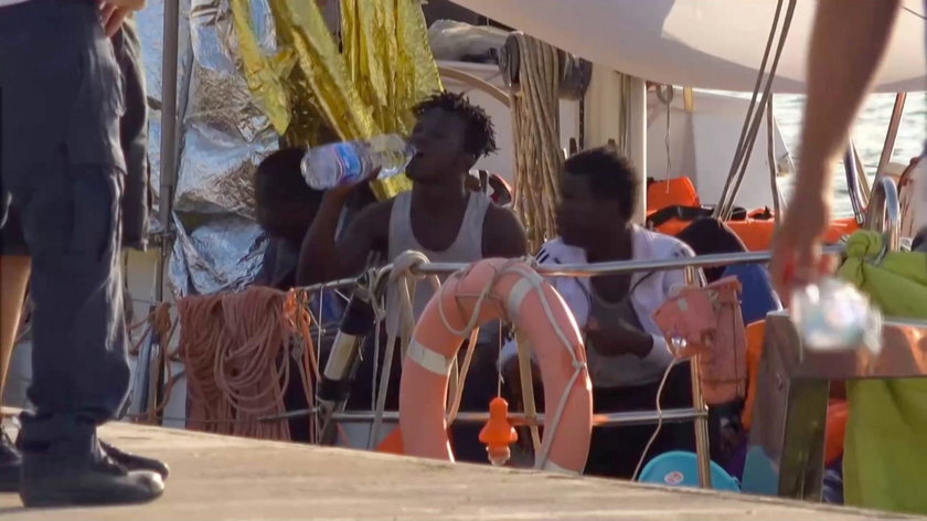 """A still image from a video footage shows migrants sitting on board of a migrant rescue boat """"Alex"""","""