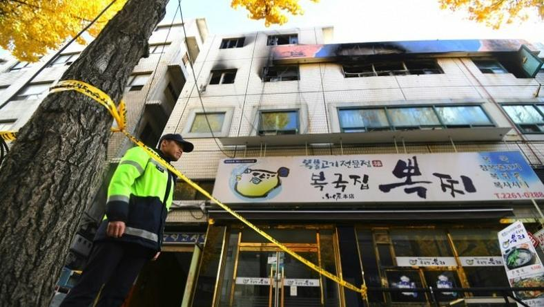 A South Korean policeman stands guard outside the scene after a fire that killed at least seven people in Seoul