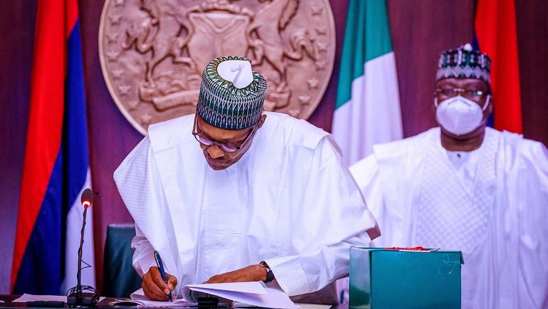 President Muhammadu Buhari signs into law the revised N10.8trn 2020 Budget as President of the Senate, Ahmad Lawan watches on. [Twitter/@Buharisallau1]