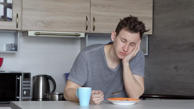 Beautiful sleepy man having breakfast at the table