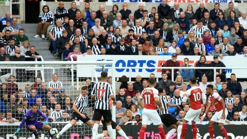 Mesut Ozil (second right) scores Arsenal's second goal in a 2-1 win away to Newcastle in the English Premier League on Saturday