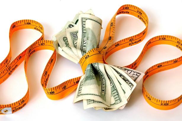 Pieniądze i metr krawiecki. Fot. Shutterstock