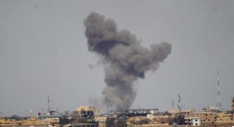 A plume of smoke rises above a building during an air strike in Tikrit March 27, 2015.
