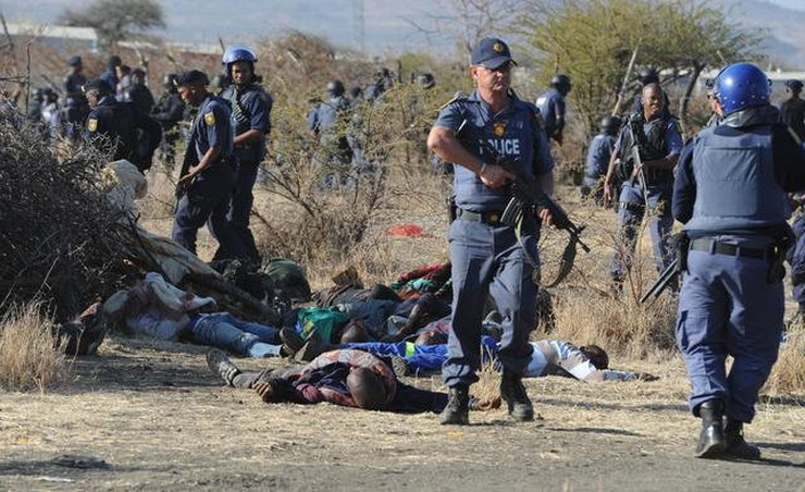 267097_police-surround-the-bodies-of-striking-miners-after-opening-fire-on-a-crowd-at-the-lonmin-platinum-mine-near-rustenburg-south-africa