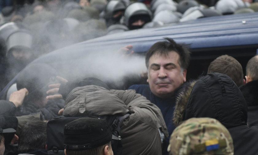 Supporters of Georgian former President Mikheil Saakashvili break a window a police car carrying Saa