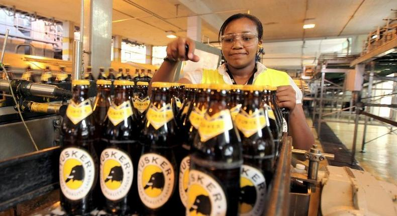 Worker inspecting beer bottles at an EABL plant