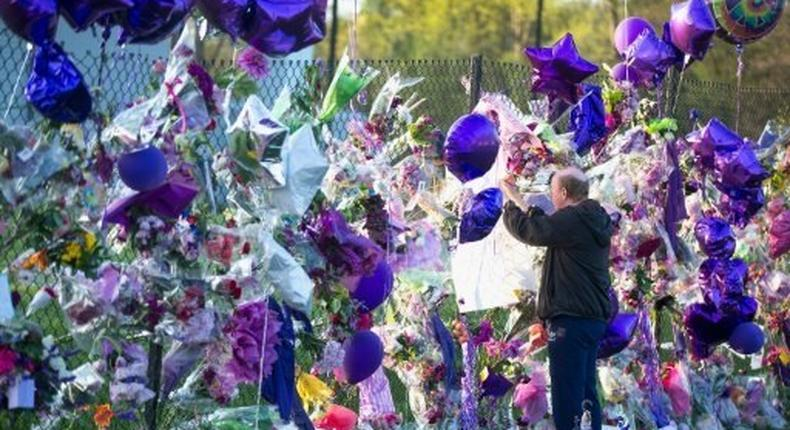A fan visits a memorial outside Paisley Park, the home and studio of Prince, in April, 2016 in Chanhassen, Minnesota