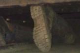 Noga jednog migranta koji se zakačio ispod kamiona viri ispod paletarnika