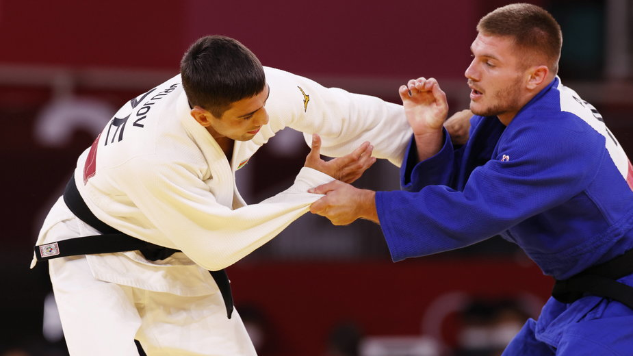 Rustam Orujov (w białym stroju) z Azerbejdżanu w walce z Akilem Gjakovejem (w niebieskim stroju) z Kosowa podczas repasażu w judo mężczyzn na IO w Tokio
