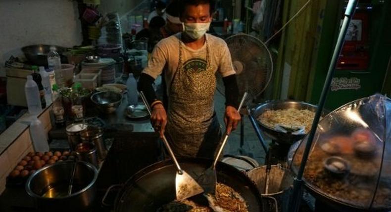 A man prepares food at a street stall in the Phrakanong district of Bangkok
