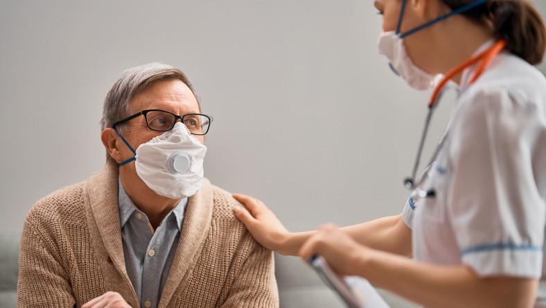Mężczyzna w maseczce badany przez lekarza