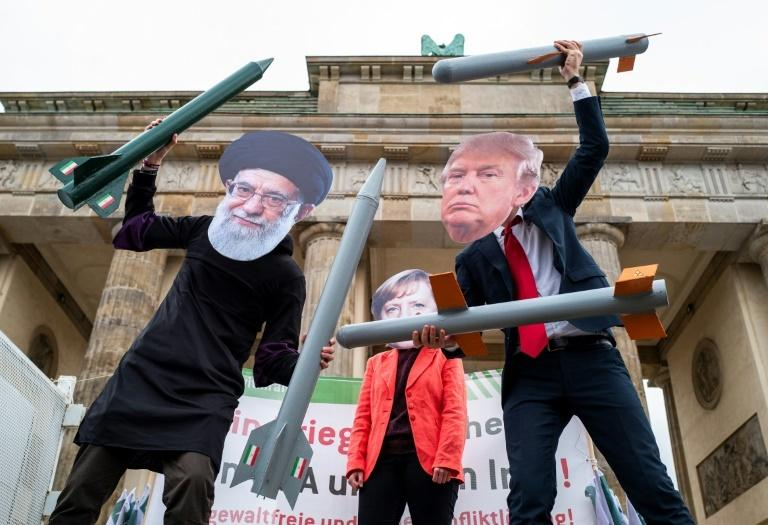 Protesters wearing masks of Iran's Supreme Leader Ali Khamenei, German Chancellor Angela Merkel and US President Donald Trump perform during an anti-war demonstration in front of Berlin's Brandenburg Gate in January 2020