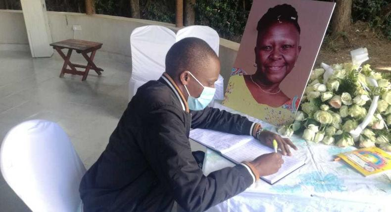 A mourner signs the condolence book for the late Jennifer Wambua