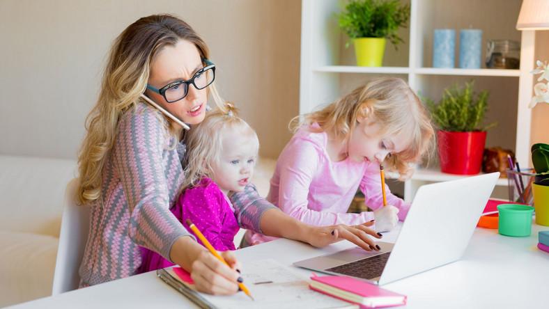 Kobieta pracuje w domu, z dziećmi