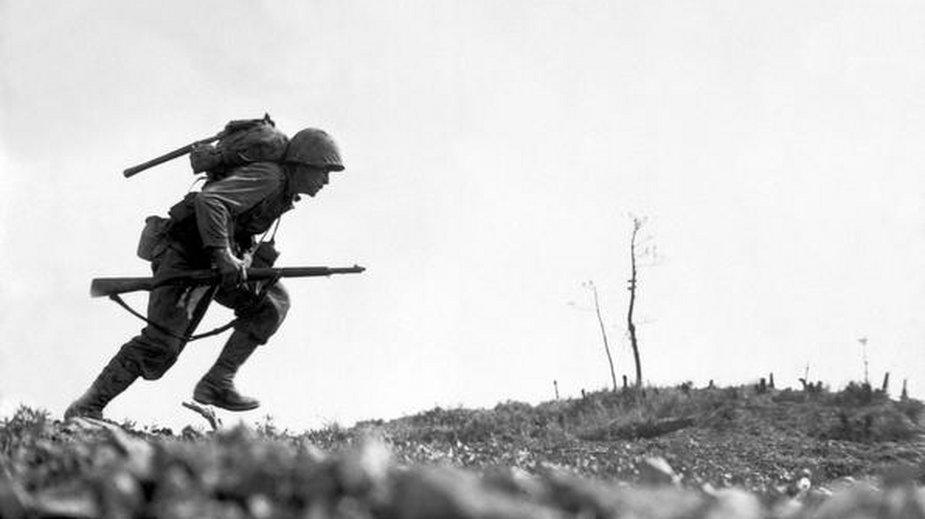 Szeregowiec Paul E. Ison z 1 Dywizji Marines biegnie przez Dolinę Śmierci na Okinawie, 10 maja 1945 roku (domena publiczna)