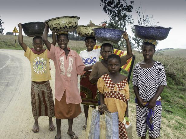 Uśmiechnięta grupa młodych mieszkańców wsi niesie w koszach zboże niedaleko hodowli bydła na ranczu Obudu. Pobliże granicy z Kamerunem. Obudu, Nigeria 2004