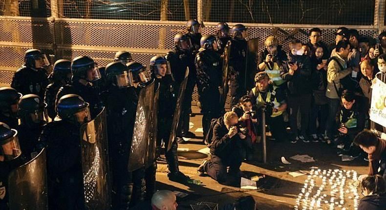 Police face demonstrators during a protest in front of the police headquarters in the 19th arrondissement of Paris on