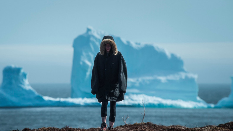 "A resident near the first iceberg of the season as it passes the South Shore, also known as ""Iceberg Alley,"" near Ferryland, Newfoundland."