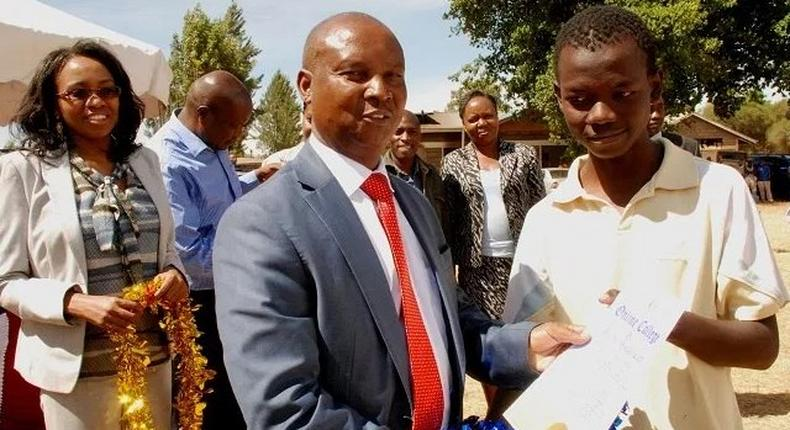 Nakuru Governor Kinuthia Mbugua awards a youth with a computer certificates for excelling in a youth empowerment program funded by the Kiamaina Bursary. The Nakuru County Public Service Board is under investigation after reports revealed that it recruited high school students as enforcement officers.
