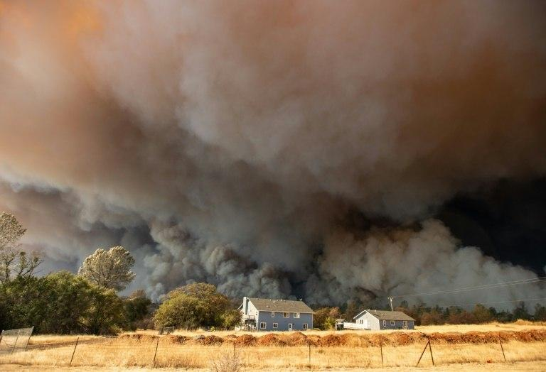 "A home is overshadowed by towering smoke plumes from the ""Camp Fire"" in Paradise, California"