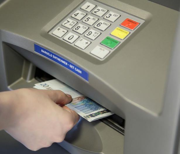 Dłoń wyciagająca banknoty z bankomatu, mat. shutterstock