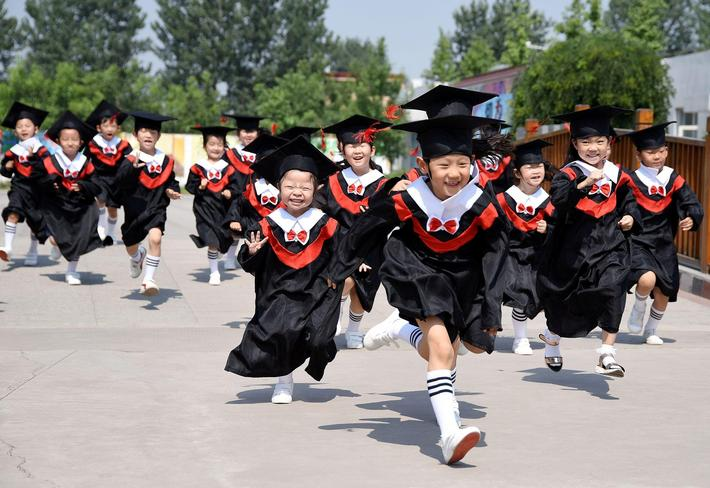 Children in gowns and mortarboards run with smiles during their kindergarten graduation ceremony in