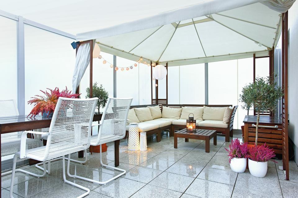 NA TARASIE przed kaprysami pogody chroni duży namiot ogrodowy rozłożony nad meblami wypoczynkowymi.