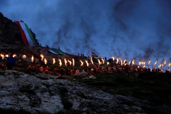 Iraqi Kurdish people carry fire torches up a mountain, as they celebrate Newroz Day, a festival mark