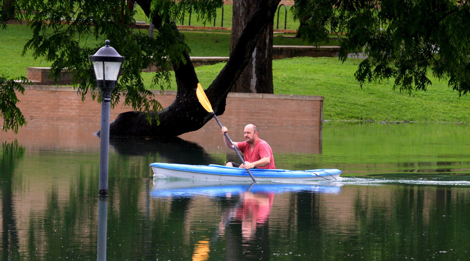 A kayaker rows through the flood waters above Sewell Park on the Texas State University campus near the headwaters of the San Marcos River in San Marcos Texas